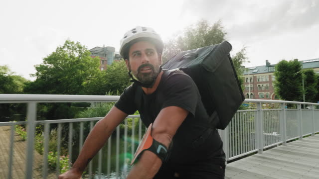 man delivering food by bike in the city - helmet stock videos & royalty-free footage