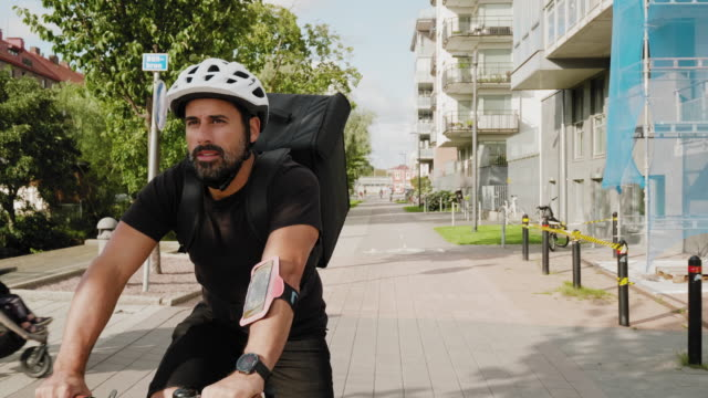 man delivering food by bike in the city - spanish and portuguese ethnicity stock videos & royalty-free footage