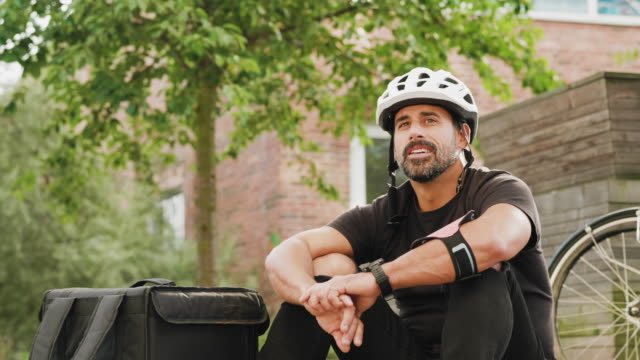 man delivering food by bike in the city - sports helmet stock videos & royalty-free footage