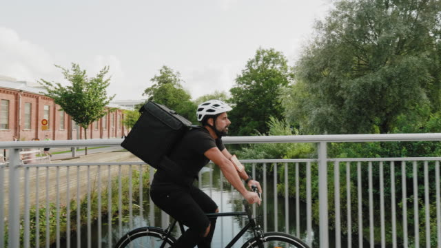 man delivering food by bike in the city - catering occupation stock videos & royalty-free footage