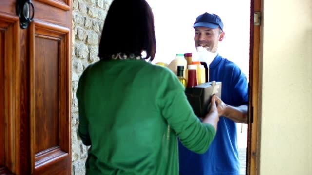 vídeos de stock, filmes e b-roll de homem entregando a comida/comida de casa - entregando