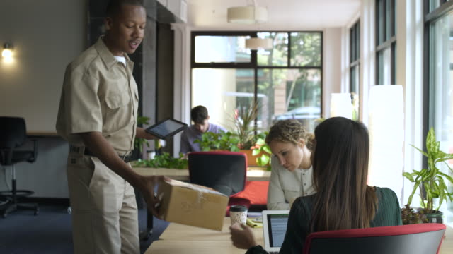 man delivering parcel to woman sitting at desk in office, signing on digital tablet. - uniform stock-videos und b-roll-filmmaterial