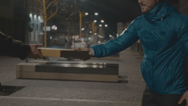 man delivering pizza box to customer on city street at night - cycling helmet stock videos & royalty-free footage