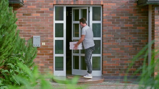 stockvideo's en b-roll-footage met mens die pizza's aan het huis van de klant zonder fysiek contact tijdens covid-19 sluiting levert - mid volwassen mannen