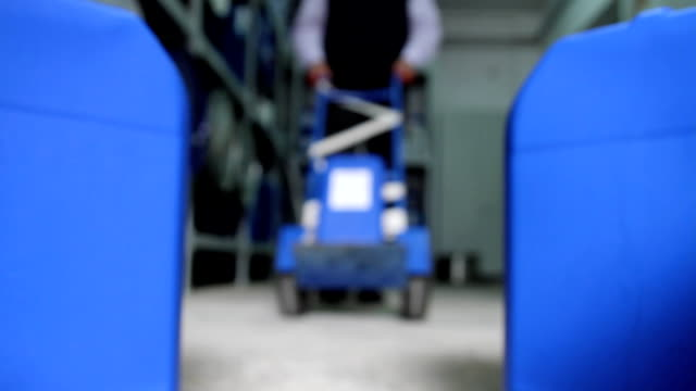 Man delivers a plastic container to a blue container storage