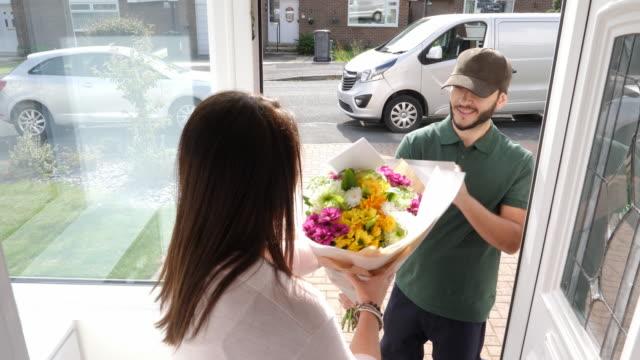 4k: mann liefert bouquet von blumen an eine frau in ihrem haus - eingangstür - liefern stock-videos und b-roll-filmmaterial
