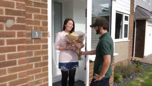 4k: man delivers bouquet of flowers to a woman at her house - front door (outdoors) - bouquet stock videos and b-roll footage