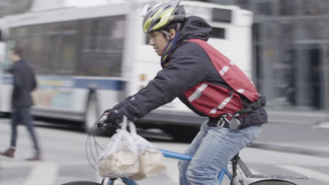 vídeos de stock, filmes e b-roll de man delivers food on bicycle in nyc - entregando