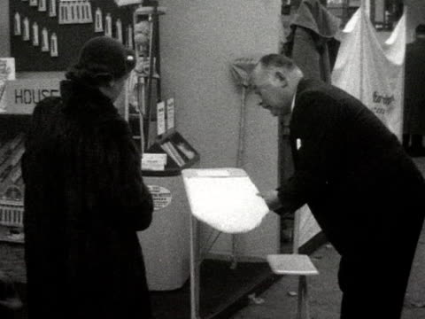 a man demonstrates an adjustable ironing board to a woman at a hardware exhibition - ironing board stock videos & royalty-free footage