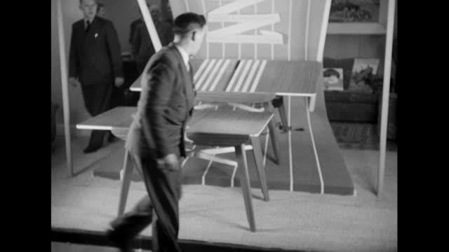A man demonstrates an extendable table at the Earls Court furniture exhibition
