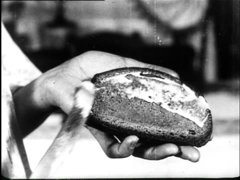 1920 b/w a man demonstrates how bread must be buttered / germany - brotsorte stock-videos und b-roll-filmmaterial