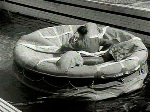 a man demonstrates the durability of a new self inflating life raft by jumping into it while it floods in a swimming pool 1954 - durability stock videos and b-roll footage