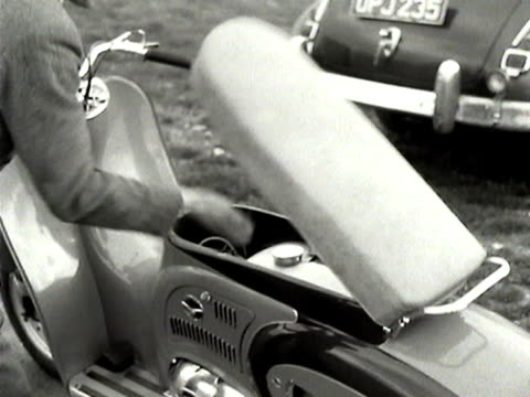 a man demonstrates the engine and fuel tank of the new dayton albatross motor scooter - 試運転点の映像素材/bロール
