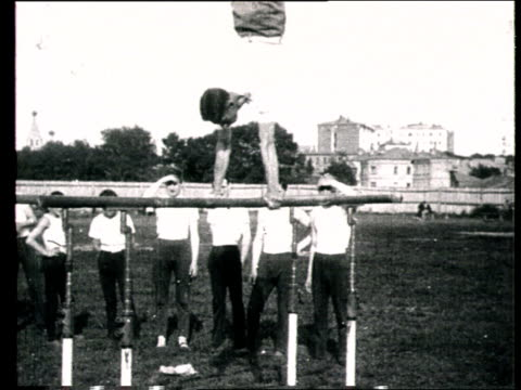 1925 b/w ws man demonstrating gymnastic routine on parallel bars/ russia - anno 1925 video stock e b–roll