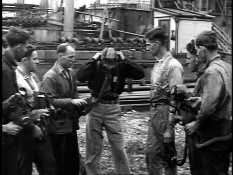 vídeos de stock, filmes e b-roll de 1929 montage man demonstrating putting on a gas mask to workers / united states - 1920 1929