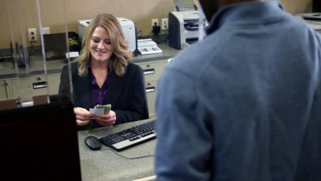 man depositing cash in bank - kassörska bildbanksvideor och videomaterial från bakom kulisserna