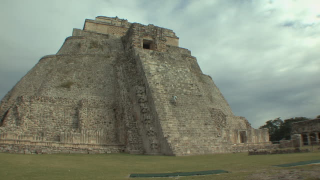 WS Man descending Adivino (Pyramid of Magician) at pre-Columbian ruined city of Maya civilization / Uxmal, Yucatan, Mexico