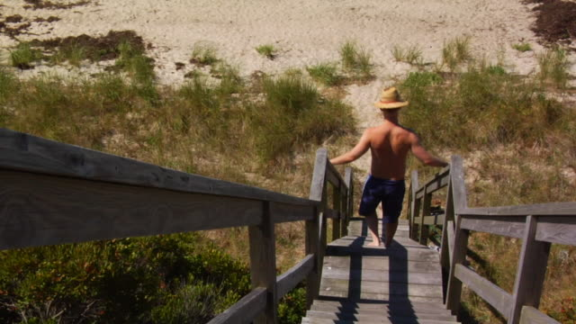 MS, TU, HA, Man descending beach stairs and walking on beach, rear view, North Truro, Massachusetts, USA
