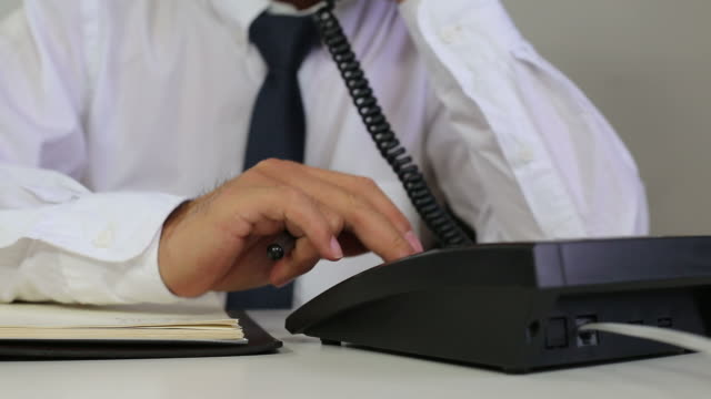man dialing the phone on the desk - file clerk stock videos & royalty-free footage