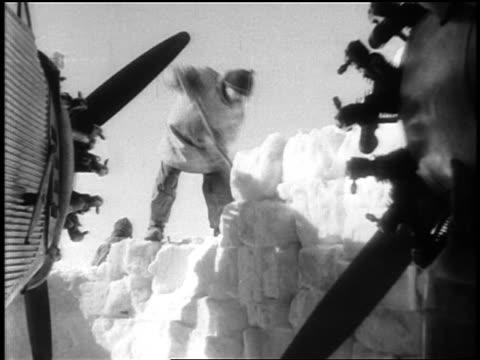 vídeos de stock e filmes b-roll de man digging away wall of snow from airplane for byrd's expedition / antarctica / docu. - pá para neve