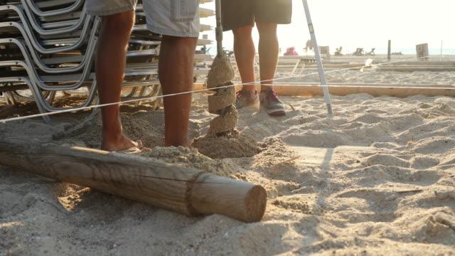 stockvideo's en b-roll-footage met man graven gat in zand met elektrische boor te installeren strand paraplu op zonnige dag - sunny
