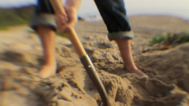 CU PAN Man digging in sand with shovel, low section / Los Angeles, California, USA