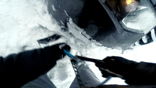 POV Man digging the car out of snow with shovel