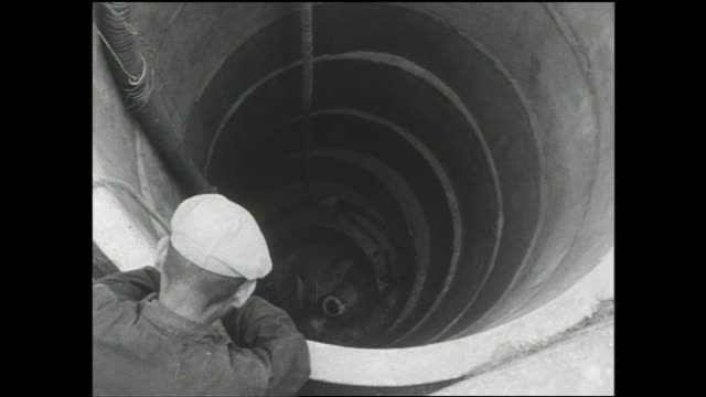 a man digs in a well as a coworker watches and water tank sections are positioned for completion. - storage tank stock videos and b-roll footage