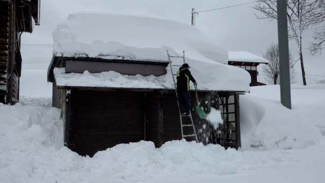 stockvideo's en b-roll-footage met man digs out after blizzard dumps huge amount of snow on village in japan - digging