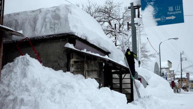man digs out after blizzard dumps huge amount of snow on village in japan - 深い雪点の映像素材/bロール