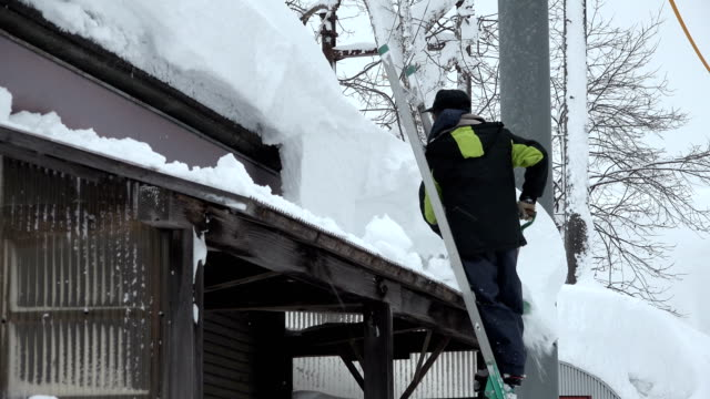 vídeos de stock, filmes e b-roll de man digs out after blizzard dumps huge amount of snow on village in japan - snow cornice