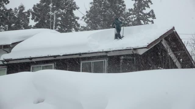 vídeos de stock, filmes e b-roll de man digs out after blizzard dumps huge amount of snow on village in northern japan - snow cornice
