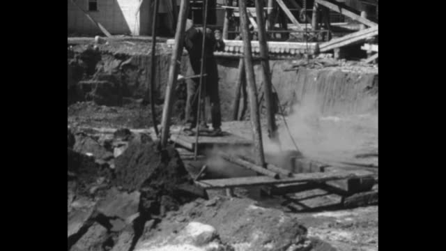 man digs out clump of oil sand from wall of pit mine with pickax / man holding small clumps in both hands squeezes oil out of them / vs man working... - ドラム容器点の映像素材/bロール