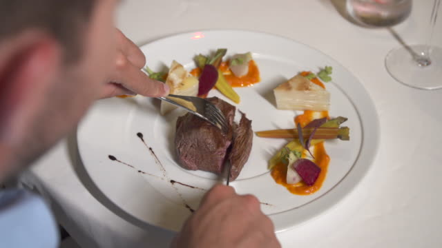 vídeos de stock e filmes b-roll de a man dining at dinner at a tropical island resort. - carne