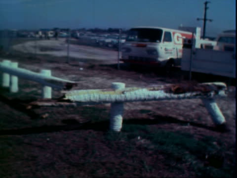 man directing automobile traffic arriving at daytona international speedway for daytona 500 / 1962 pontiac stock car broken wood barriers following... - 1959 stock-videos und b-roll-filmmaterial