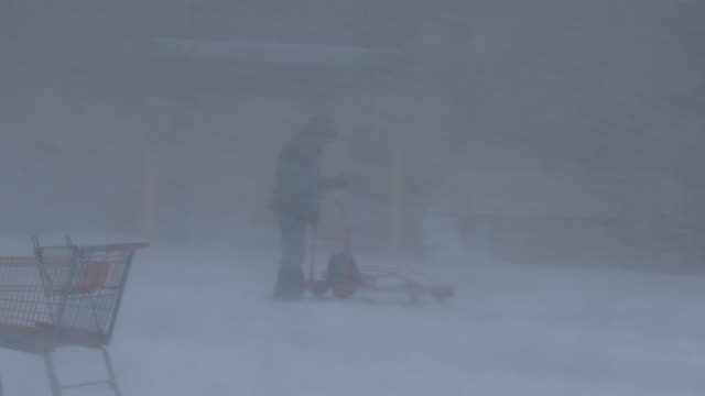 A man disappears behind a wall of white as powerful winds combine with very heavy snow creating complete whiteout conditions during a blizzard in...