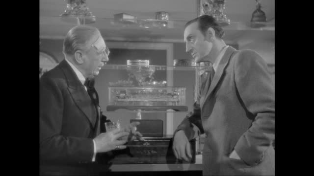 1946 man discusses his stolen music box with sherlock holmes (basil rathbone) - sherlock holmes stock videos & royalty-free footage