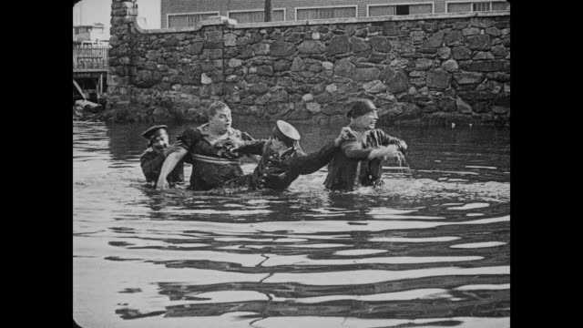 stockvideo's en b-roll-footage met 1917 man (fatty arbuckle) disguised as woman fights with man in ocean until police officers drag both men out of the water - 1917