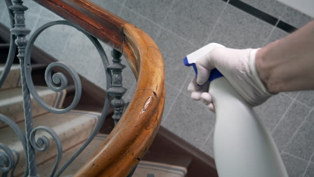 man disinfecting staircase handrail - bannister stock videos & royalty-free footage
