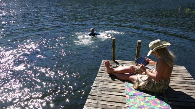 Man dives into lake wearing wetsuit, woman takes pic