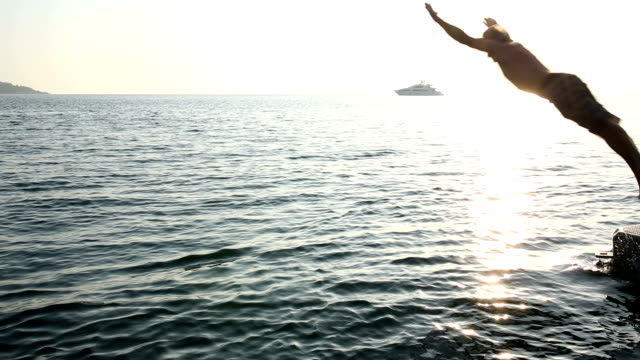 Man dives into sea from pier, sunrise