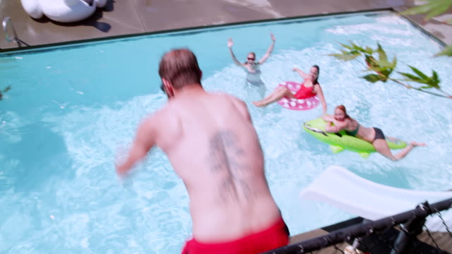 ms ts slo mo man diving from wall into outdoor pool with friends watching in background - swimming shorts stock videos & royalty-free footage