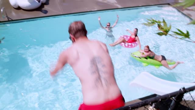 ms ts slo mo man diving from wall into outdoor pool with friends watching in background - badbyxor bildbanksvideor och videomaterial från bakom kulisserna
