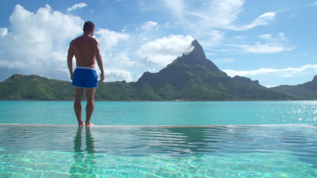 a man diving in a pool, lifestyle in a pool on bora bora with mount otemanu at a tropical island resort. - デッキ点の映像素材/bロール