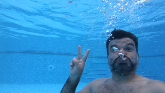 man tauchen in den pool - winken stock-videos und b-roll-filmmaterial