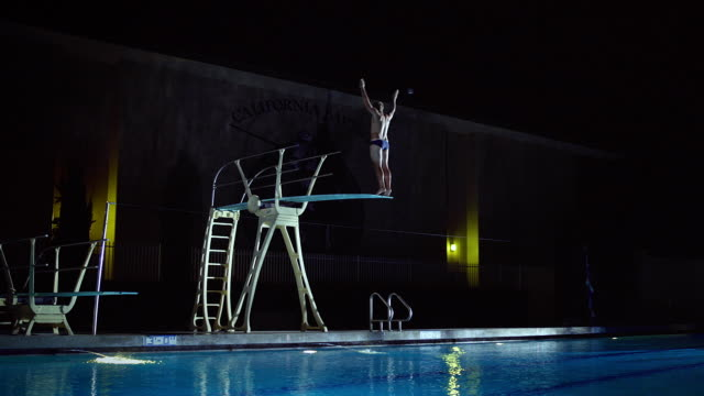 ws slo mo man diving in swimming pool / riverside, california, united states - 水に飛び込む点の映像素材/bロール
