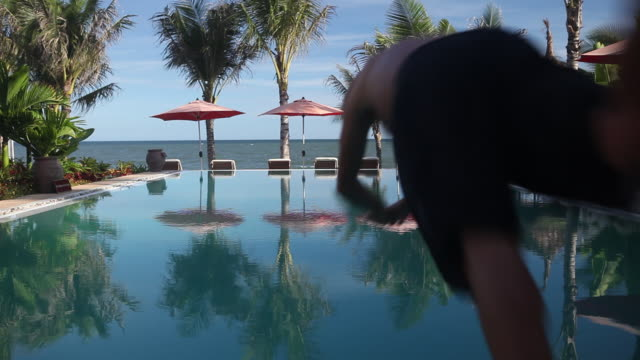 WS Man diving into infinity pool with palm trees and parasols and sea in background
