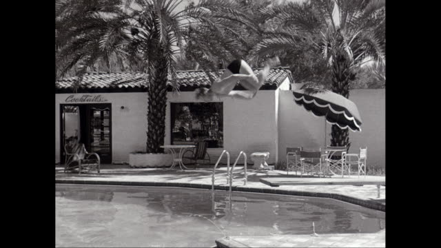 ms man diving into swimming pool at resort / united states - diving platform stock videos and b-roll footage