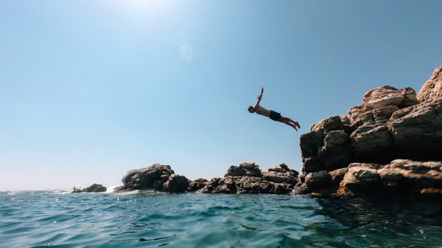 man diving into the sea from a rock - boomerang video effect - rock stock videos & royalty-free footage