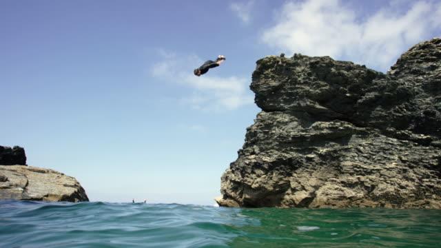 man diving off cliffs into the sea. - 崖点の映像素材/bロール